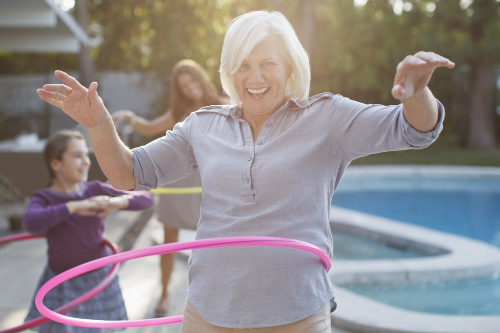 Retired woman playing spinning a hula hoop with her family.